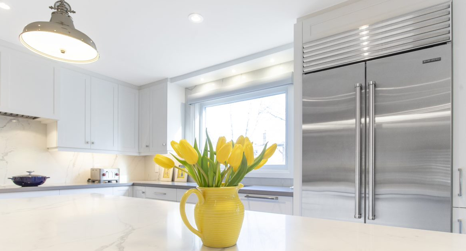 Sub-zero fridge behind a yellow vase with yellow tulips