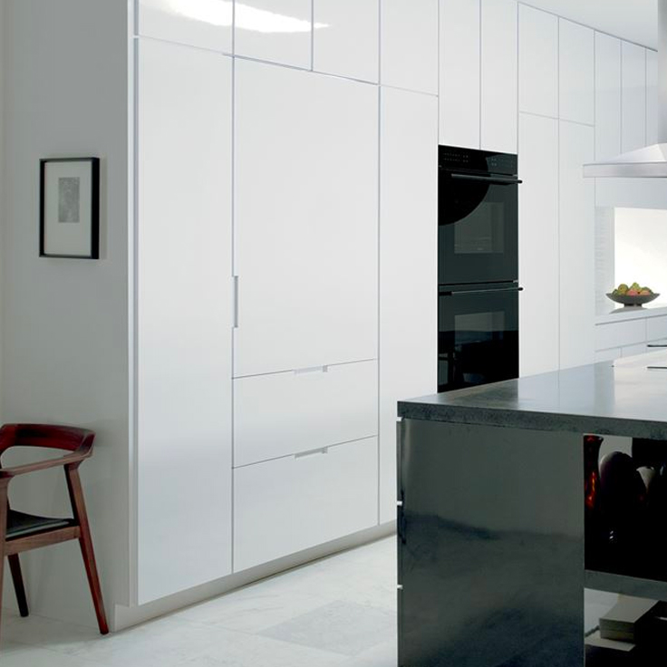 Integrated Sub-Zero fridge beside Wolf wall ovens in kitchen image